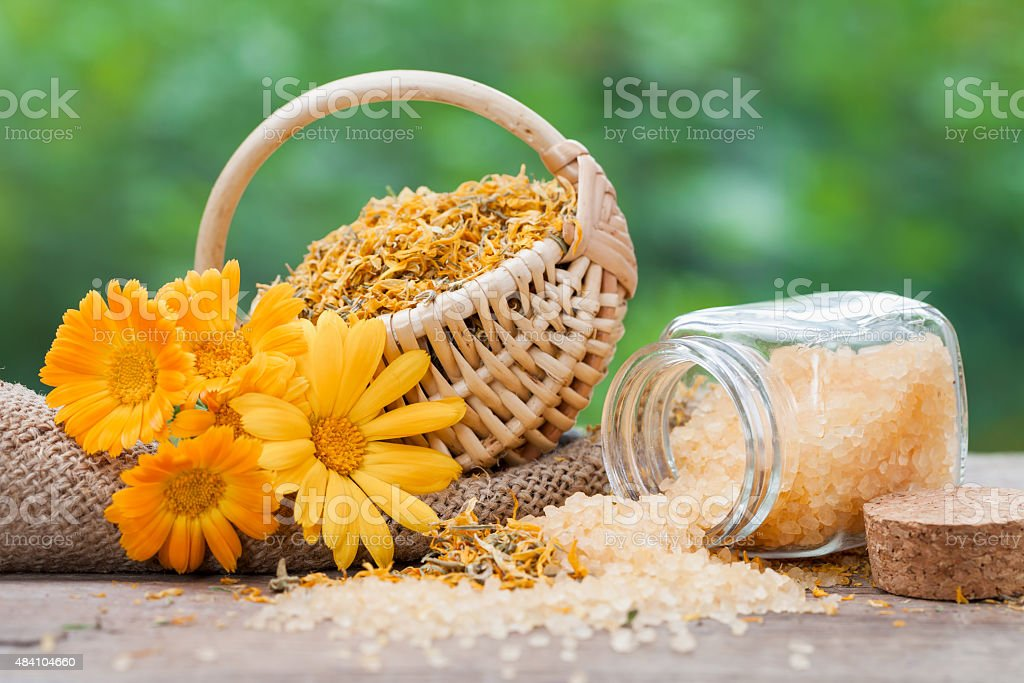 Marigold flowers, basket with dried plants and sea salt stock photo