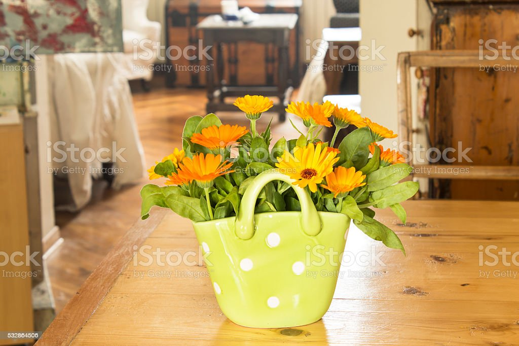 Marigold in a basket on a wooden table in the living room stock photo