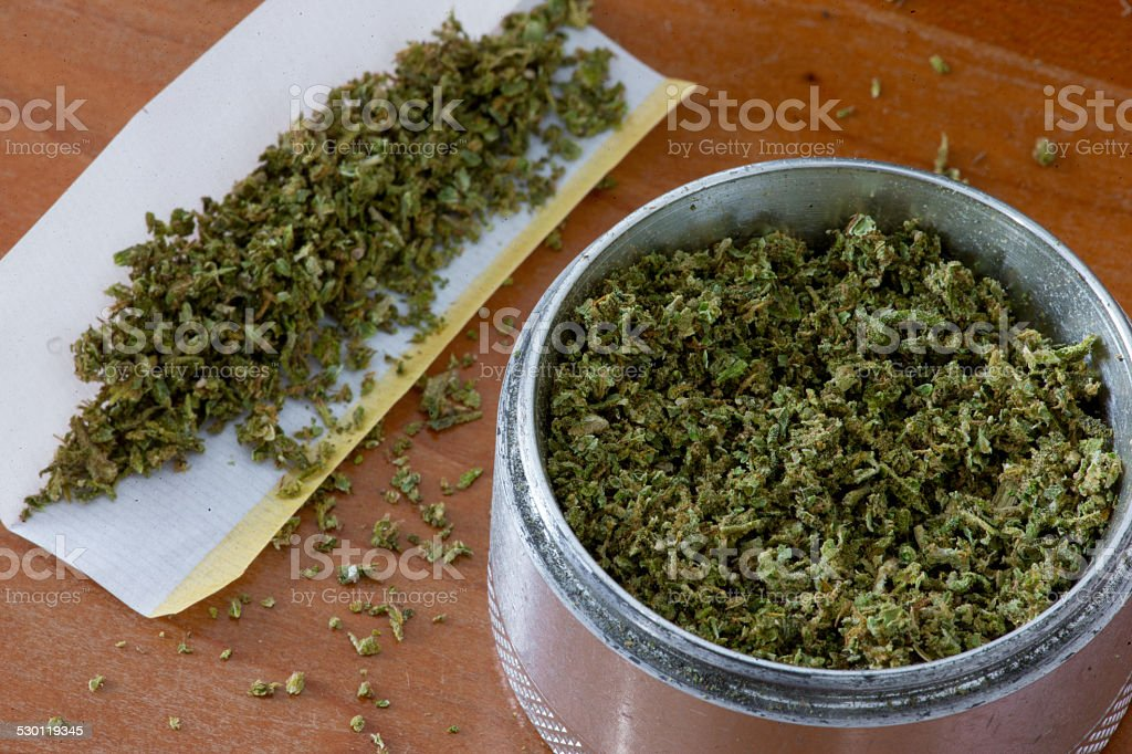 Marijuana grinder and rolling paper for a joint stock photo