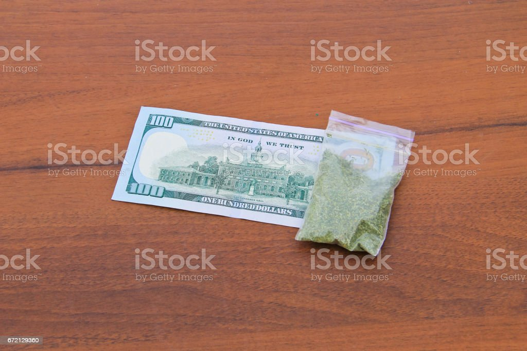 Marijuana in packet and 100 dollar bill on the wooden table stock photo