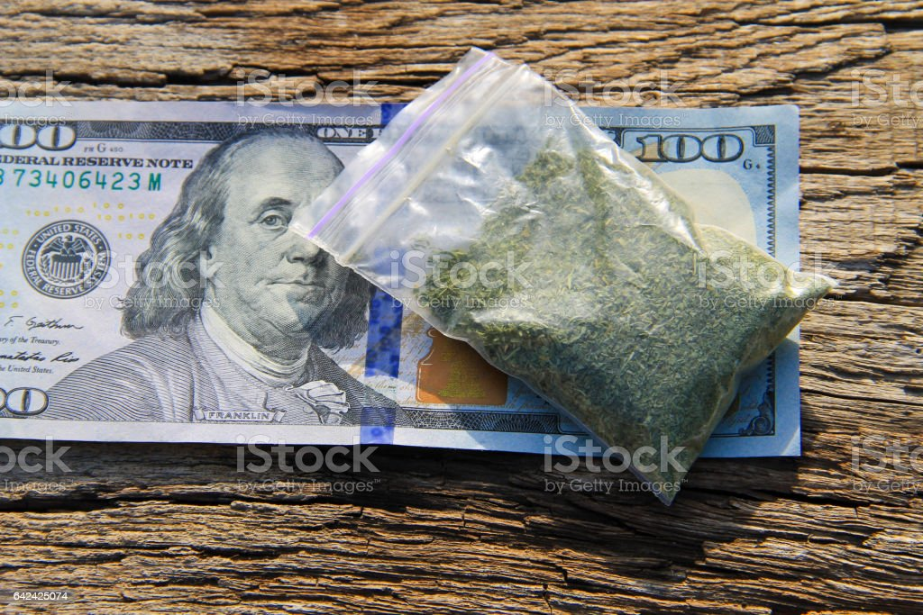 Marijuana in packet and 100 dollar bill on wooden table stock photo