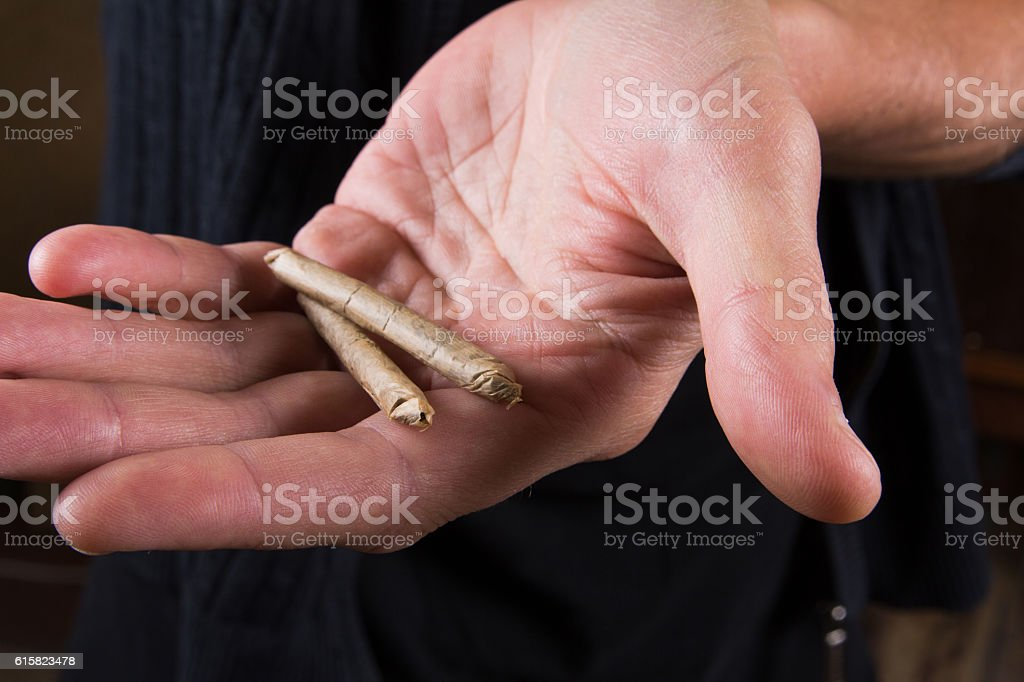 Marijuana joints in the mans hand. Man offering drugs stock photo