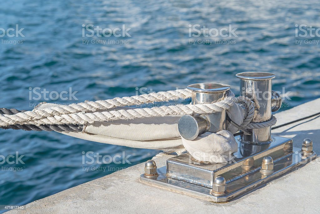 Marina bollard (bitt) at jetty for mooring with rope stock photo