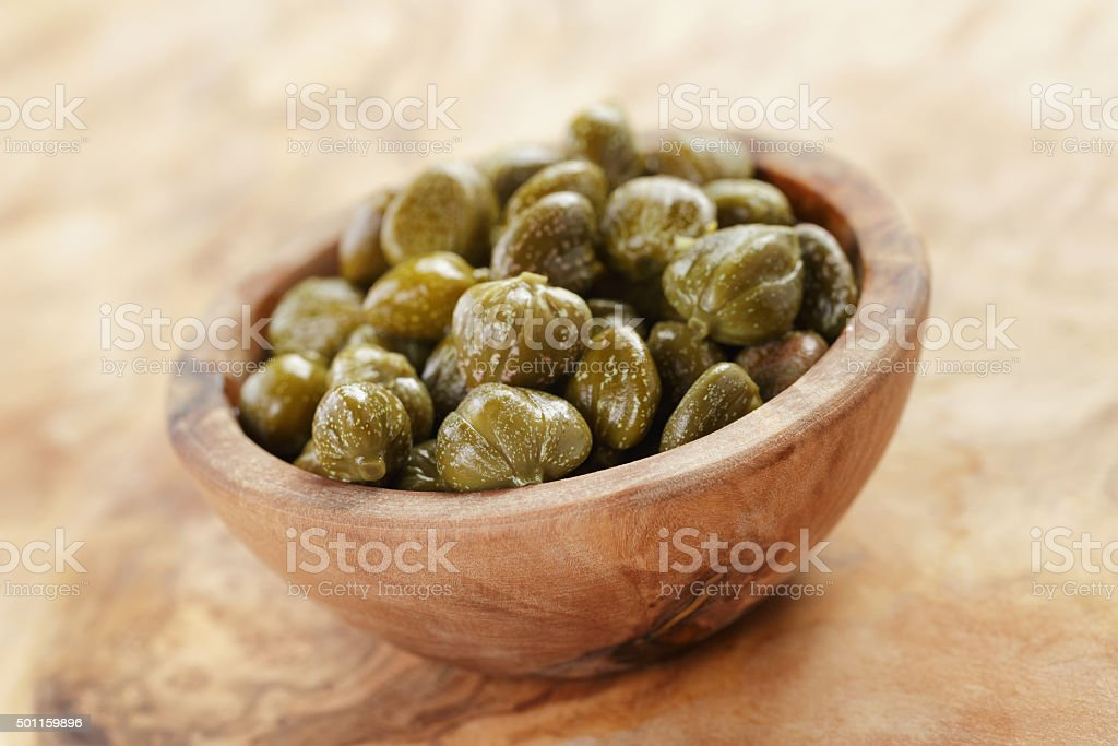 marinated capers in bowl on olive board stock photo