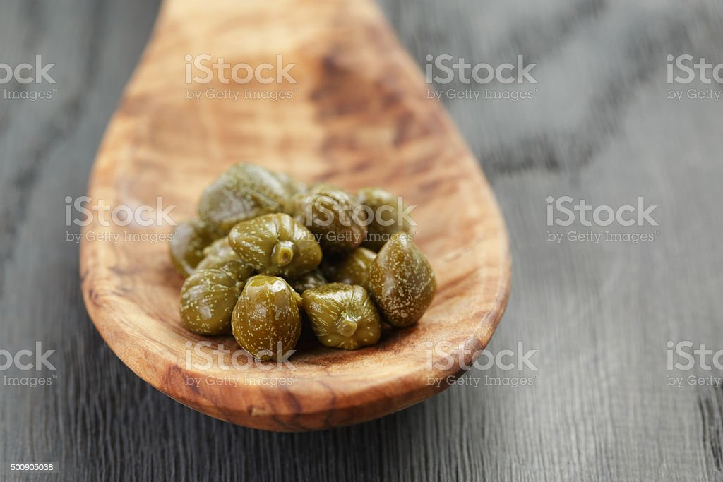 marinated capers in wood spoon on table stock photo