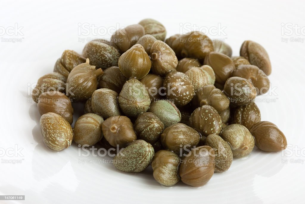Marinated capers piled up against a white background royalty-free stock photo