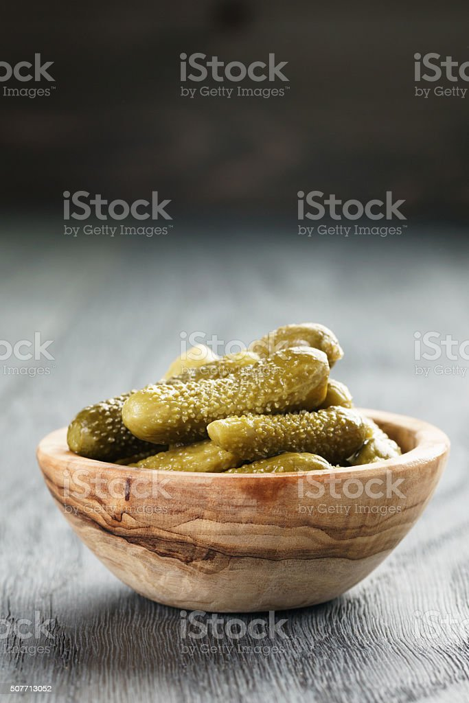 marinated cornichons in wooden bowl stock photo