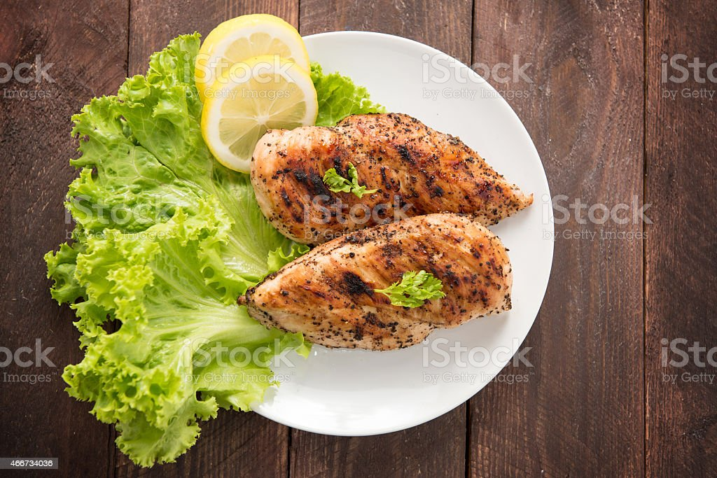 Marinated grilled chicken breasts cooked BBQ and served with fre stock photo