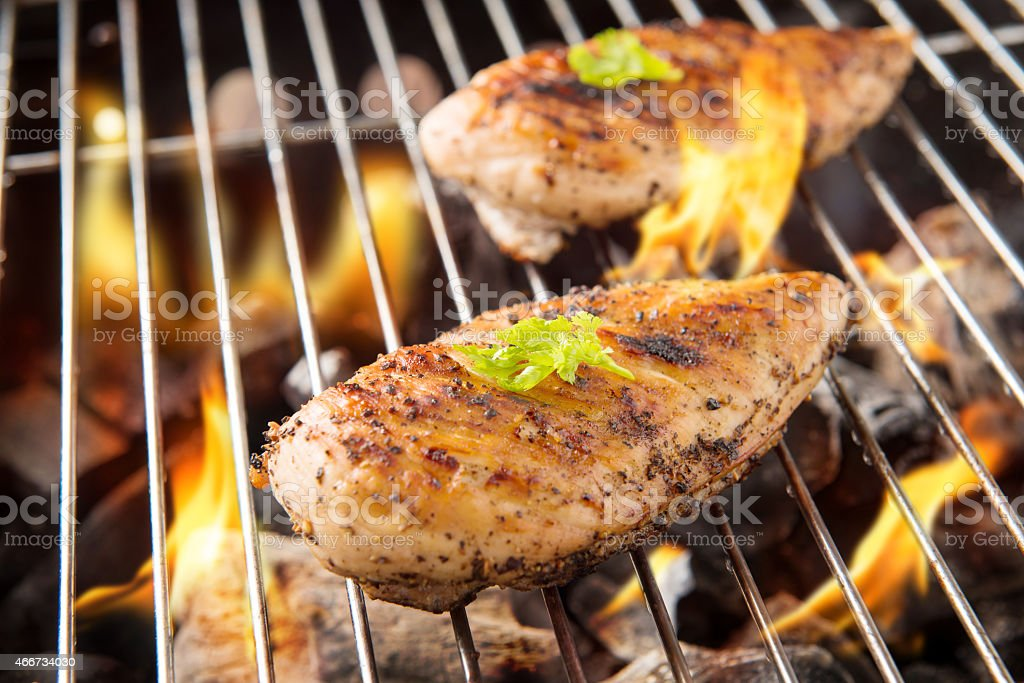 Marinated grilled chicken on the flaming grill stock photo