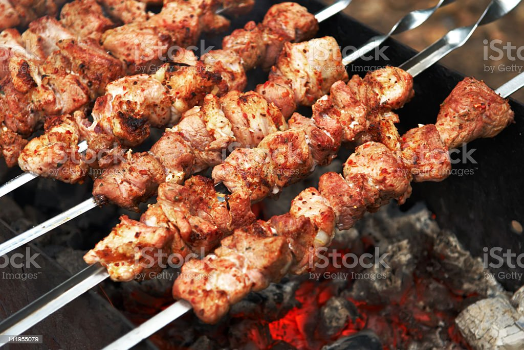 Marinated pork kebabes roasting on open coal grill royalty-free stock photo