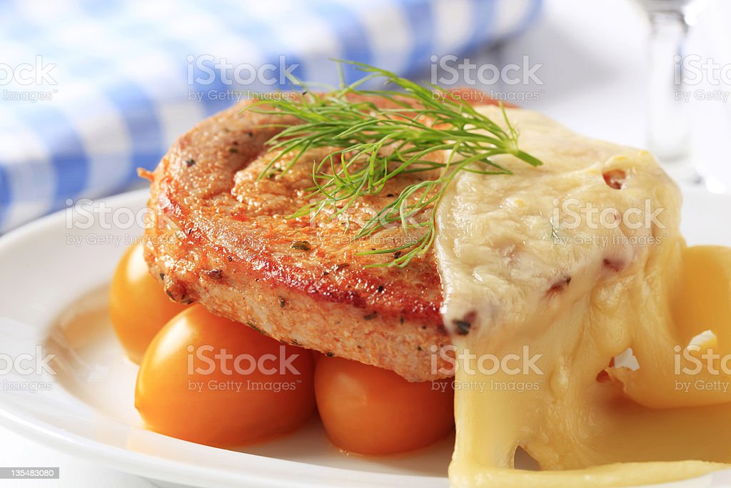 Marinated pork  topped with Swiss cheese stock photo