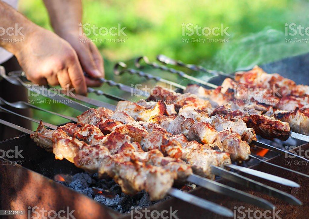 Marinated shashlik, lamb meat grilling on metal skewer, close up stock photo
