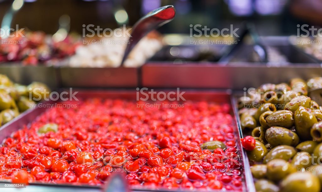 Marinated small red peppers in olive bar macro closeup stock photo
