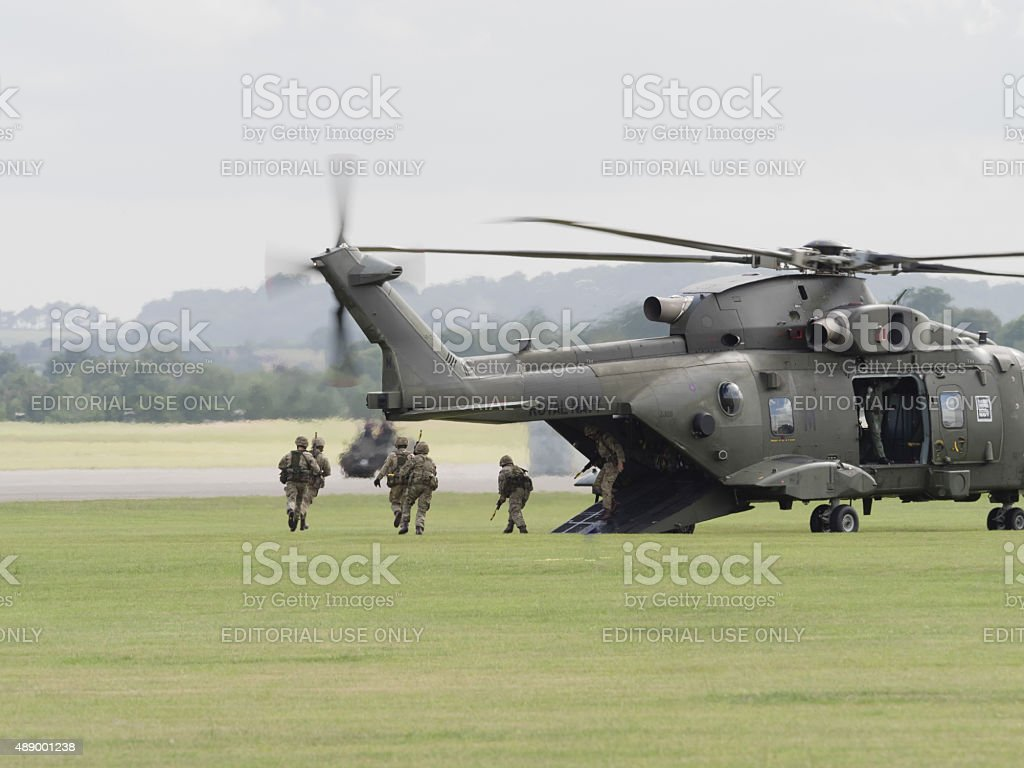 Marines disembarking a Royal Navy Merlin helicopter stock photo