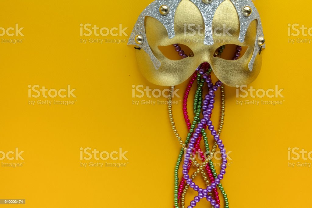 Maris gras mask and beads on yellow background with copy stock photo