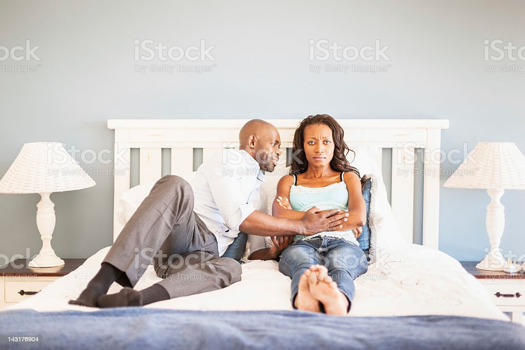 Marital Problems Sulking Wife and Pleading Husband in Bedroom stock photo