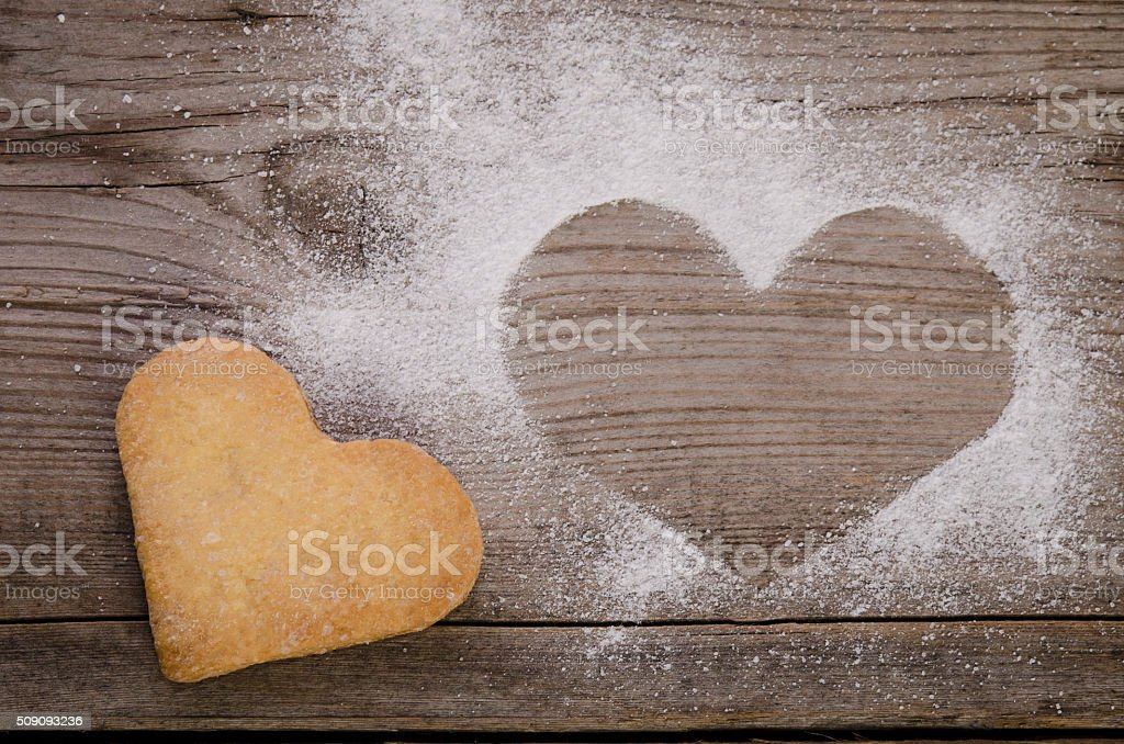 mark in shape of heart with powdered sugar and cookie-heart stock photo