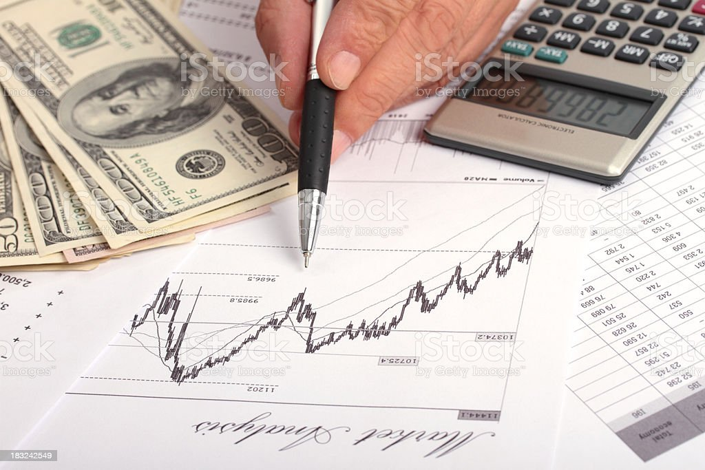 Market analysis with US dollar bills and calculator royalty-free stock photo