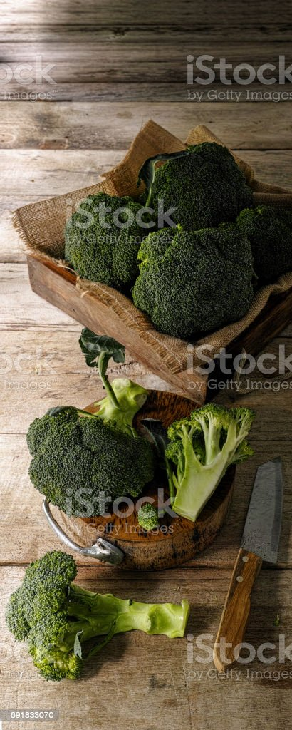 Market fresh broccoli sliced into pieces on an old wooden cutting board alongside a sharp knife on an old weathered wooden table background, with more broccoli spears on burlap material in a wooden crate in the background. stock photo
