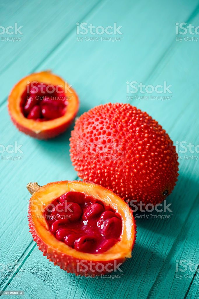 Market fresh Gac fruit on an old wooden table. stock photo