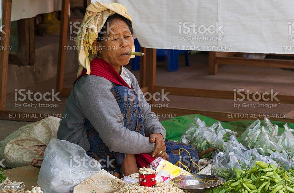 Market lady smoking cigar stock photo