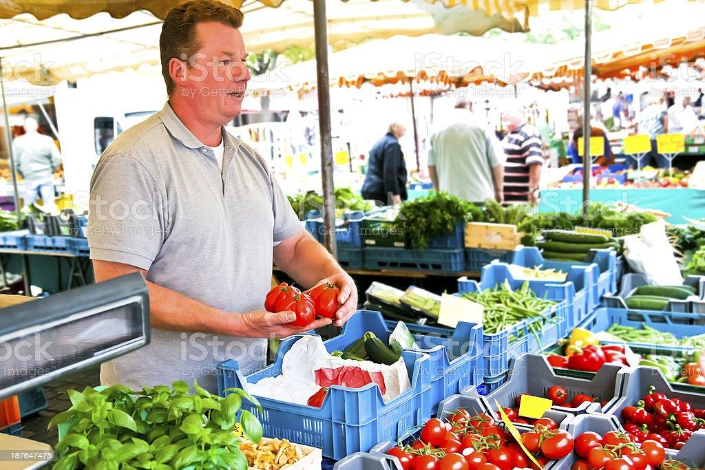 Market vendor offers giant tomatoes stock photo