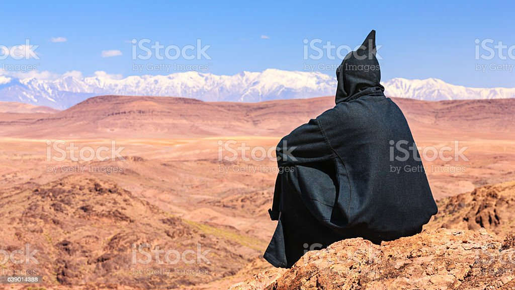 Maroccan man looking at High Atlas mountain range stock photo