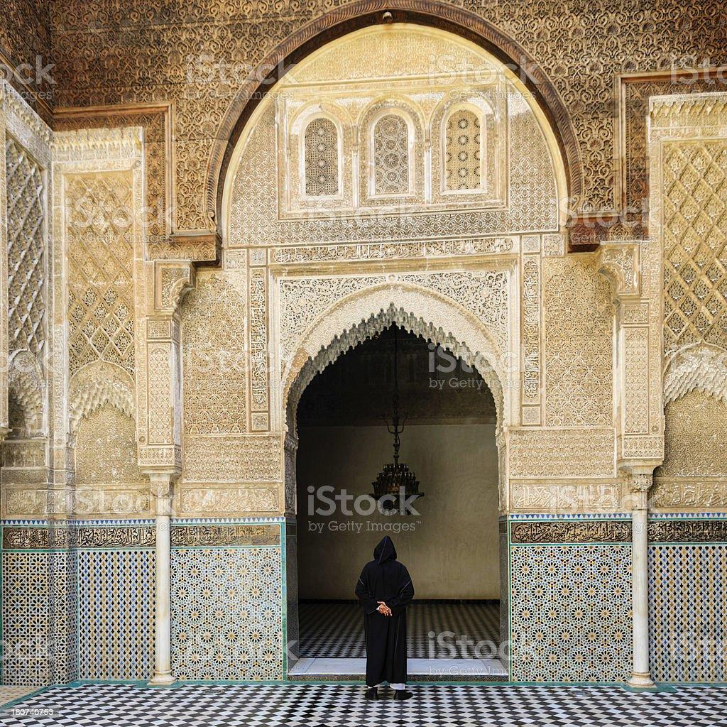 Maroccan man walking inside of Attarin Medersa in Fes, Morocco stock photo