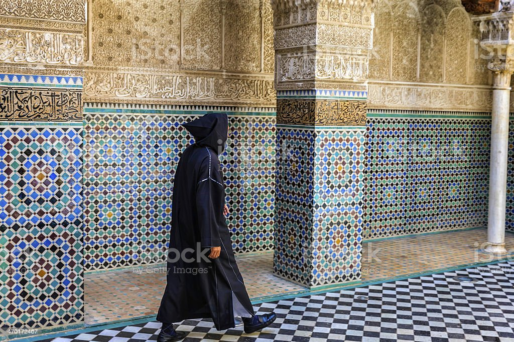 Maroccan man walking inside of Attarin Medersa in Fes, Morocco royalty-free stock photo