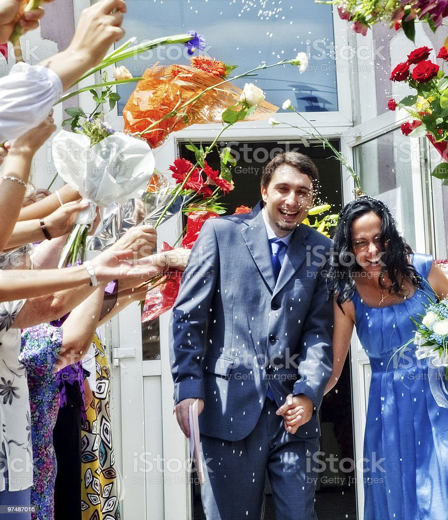 Marriage celebration - husband wife rice and flowers royalty-free stock photo