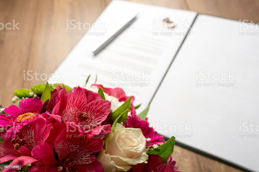 Marriage Contract and Bouquet of Flowers on Table stock photo