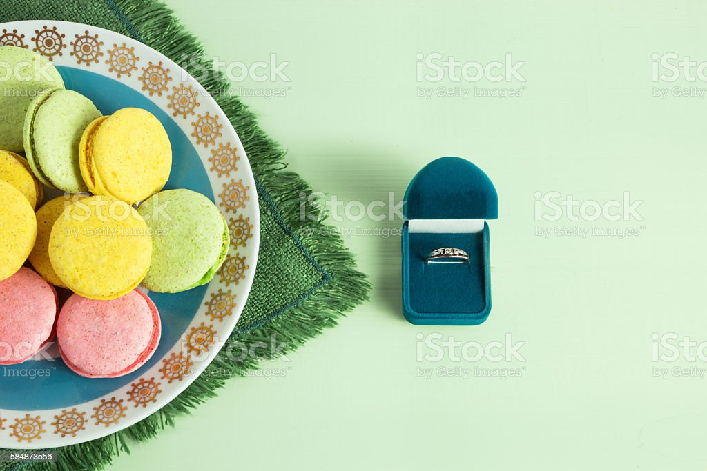 Marriage proposal, box with a ring and macaroon on mint stock photo