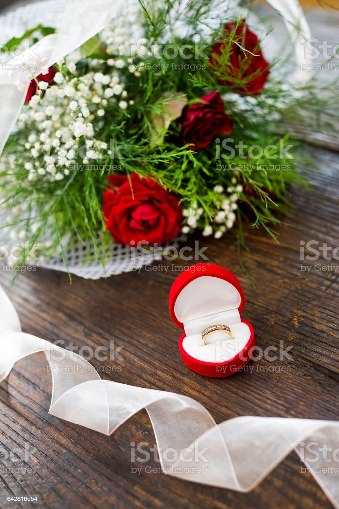 Marriage proposal with gold ring and red roses stock photo