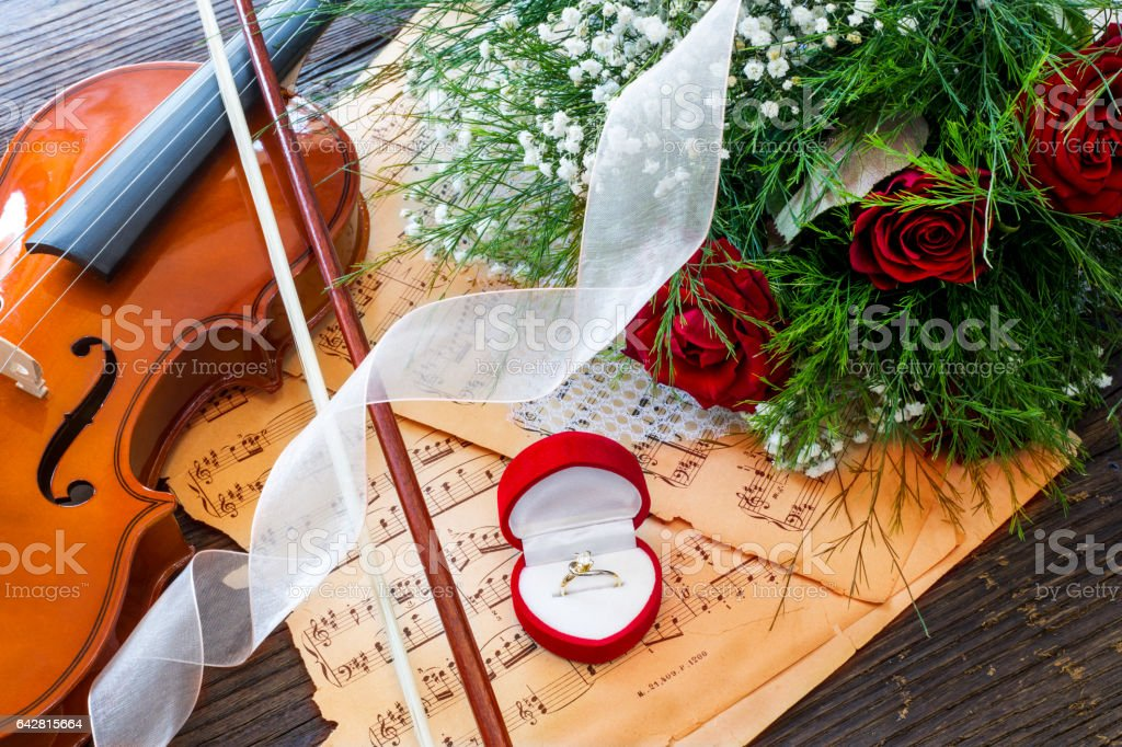 Marriage proposal with gold ring, red roses and violin on music notes stock photo