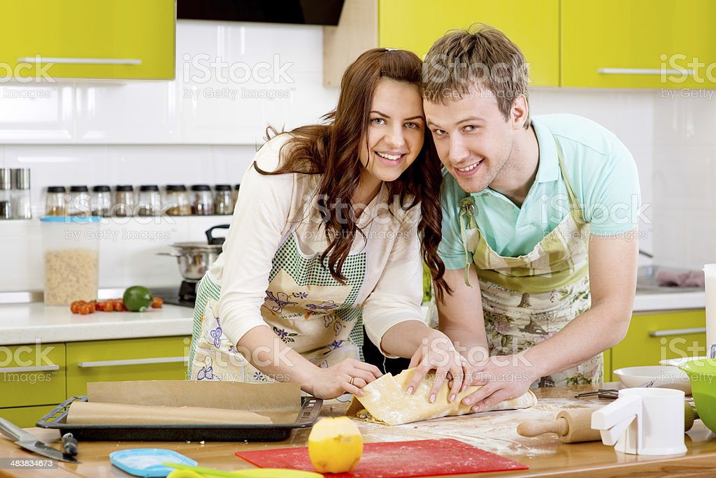 Married couple cooking apple pie at the kitchen in home royalty-free stock photo
