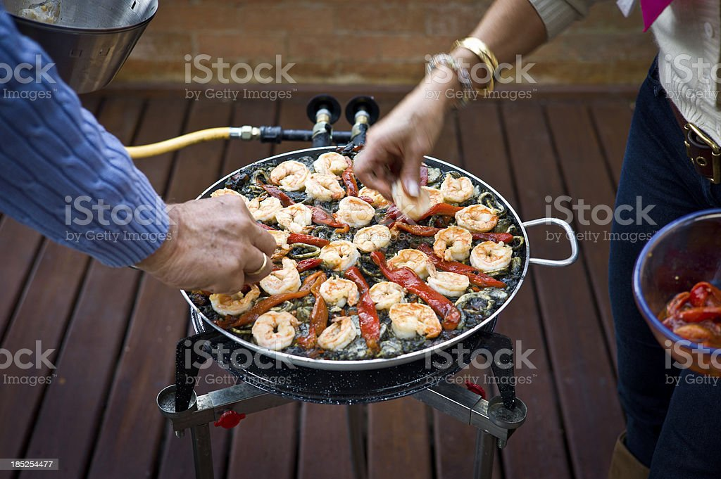 Married Couple Making a Black Paella Together stock photo