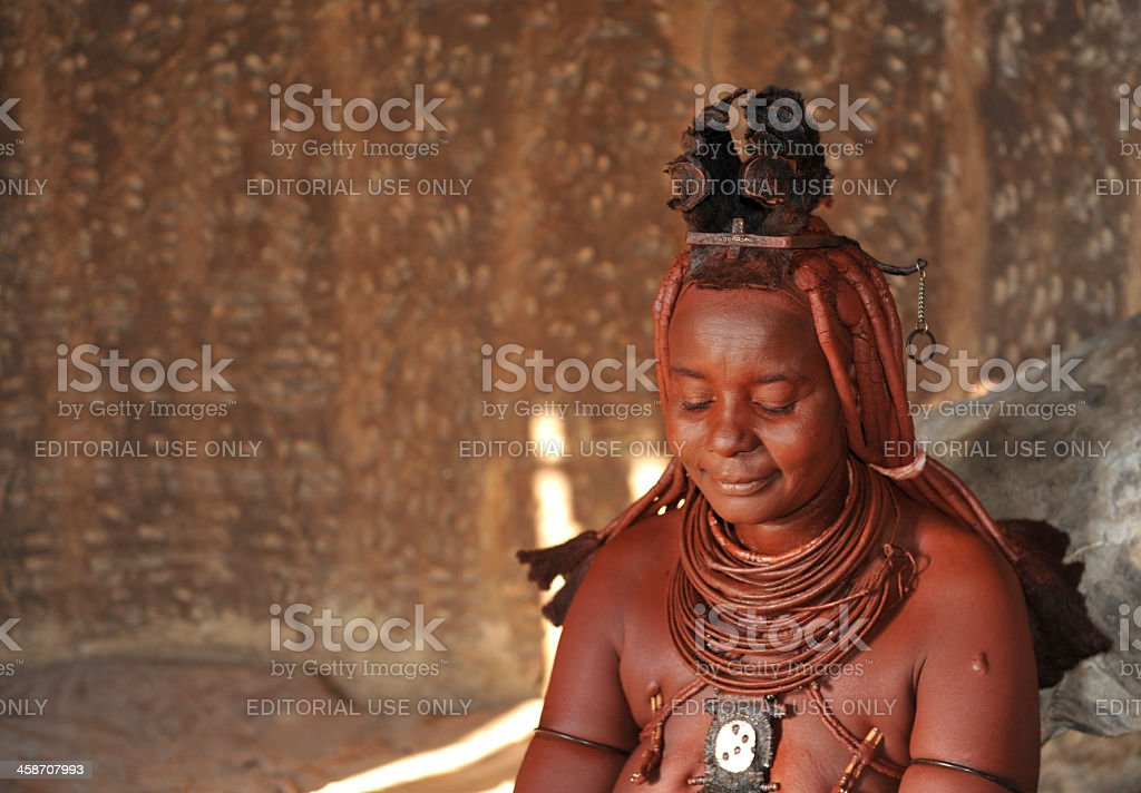 Married Himba woman inside hut in village near Opuwo,Namibia stock photo