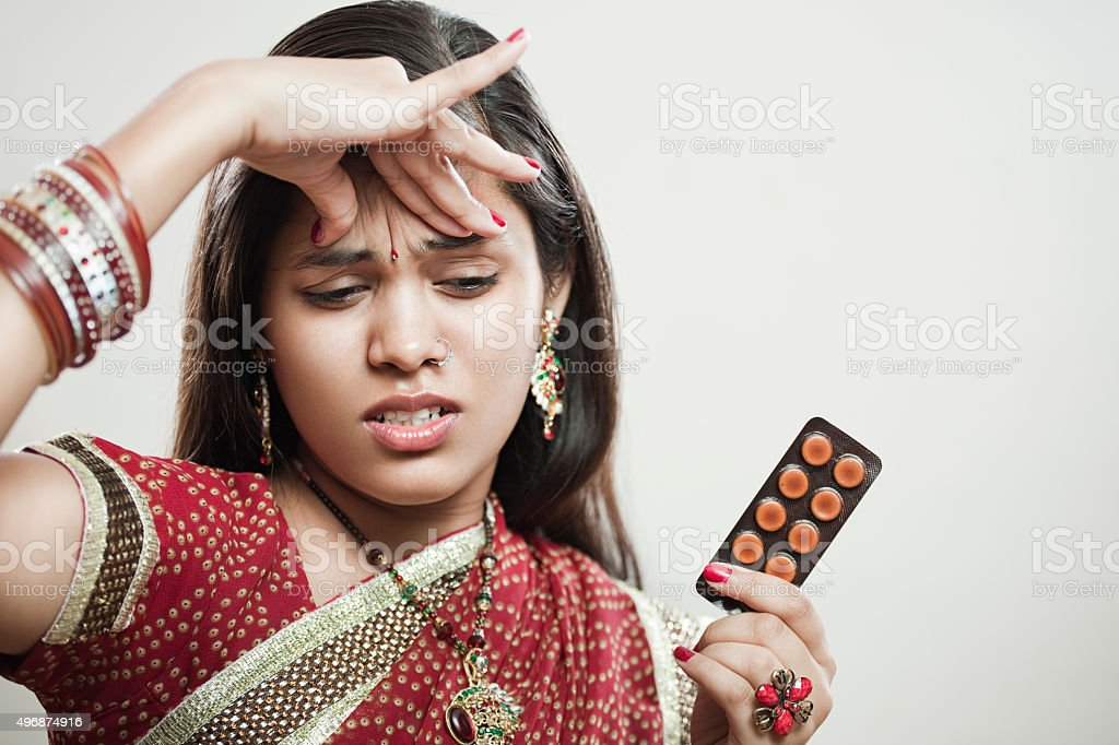 Married Hindu young woman holding head and pills. stock photo