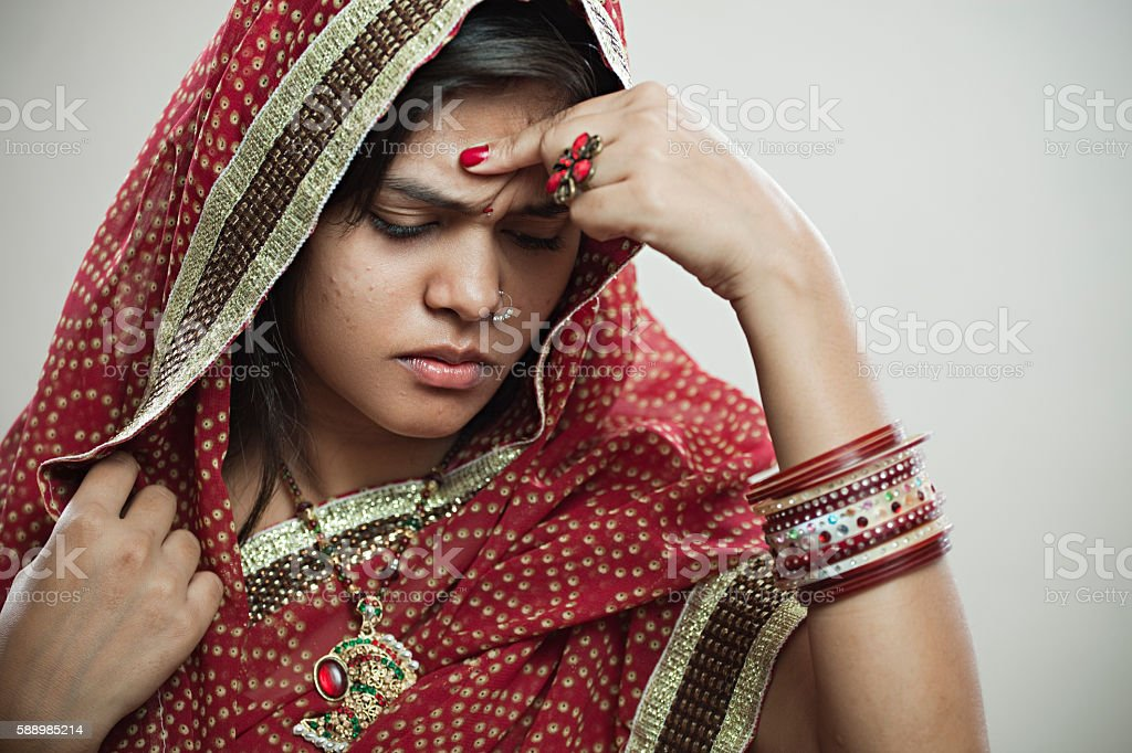 Married Hindu young woman holding head out of headache. stock photo