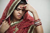 Married Hindu young woman holding head out of headache.