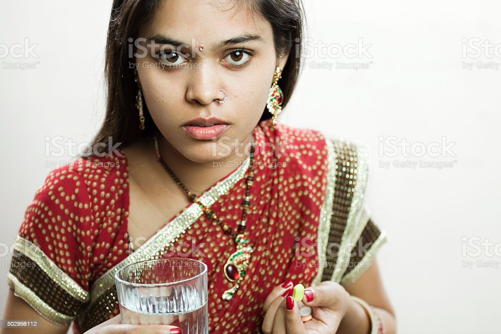 Married Hindu young woman holding pills and glass of water. stock photo
