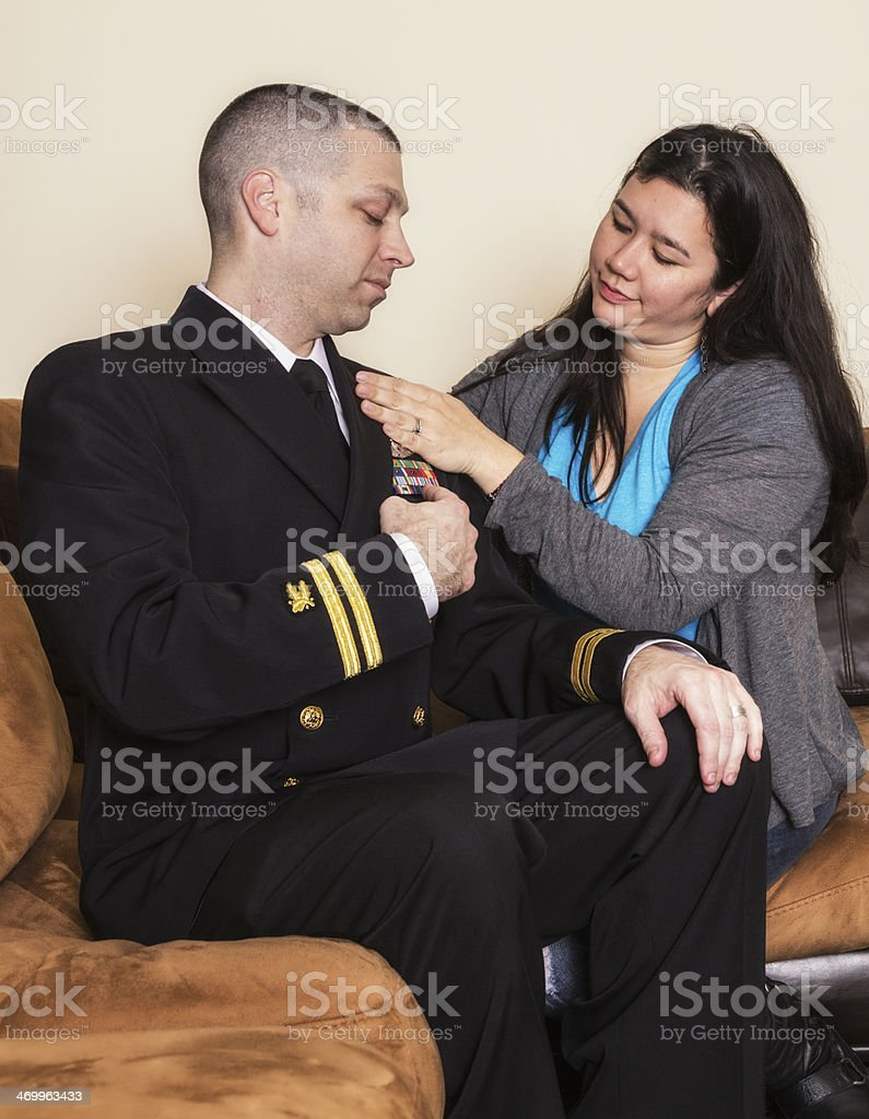 Married Military Couple Discussing US Navy Officer Uniform Ribbons stock photo