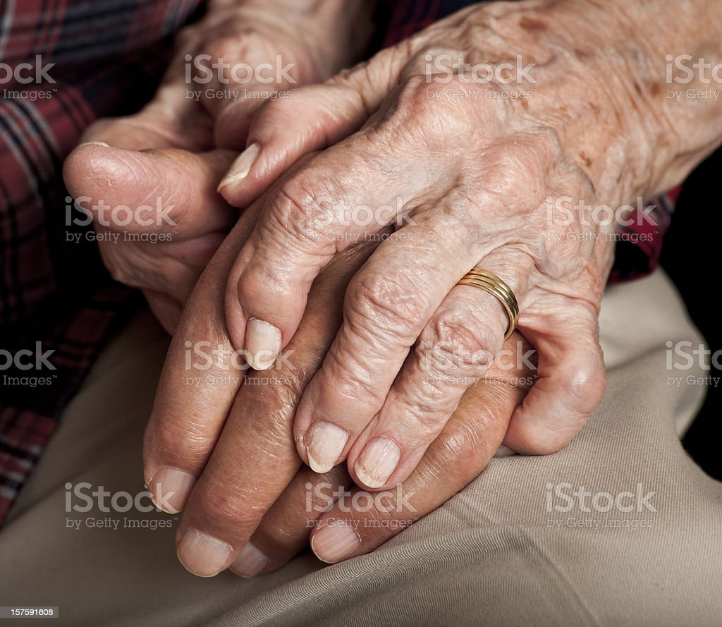 married senior couple holding hands stock photo