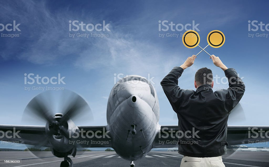 Marshaller stopping an aircraft on runway stock photo