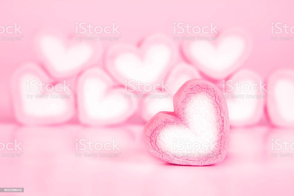 marshmallow heart shape in cup on pink background stock photo