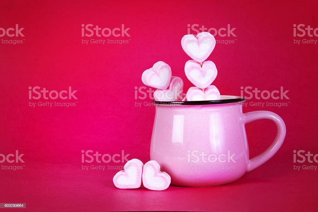 marshmallow heart shape in cup on pink stock photo