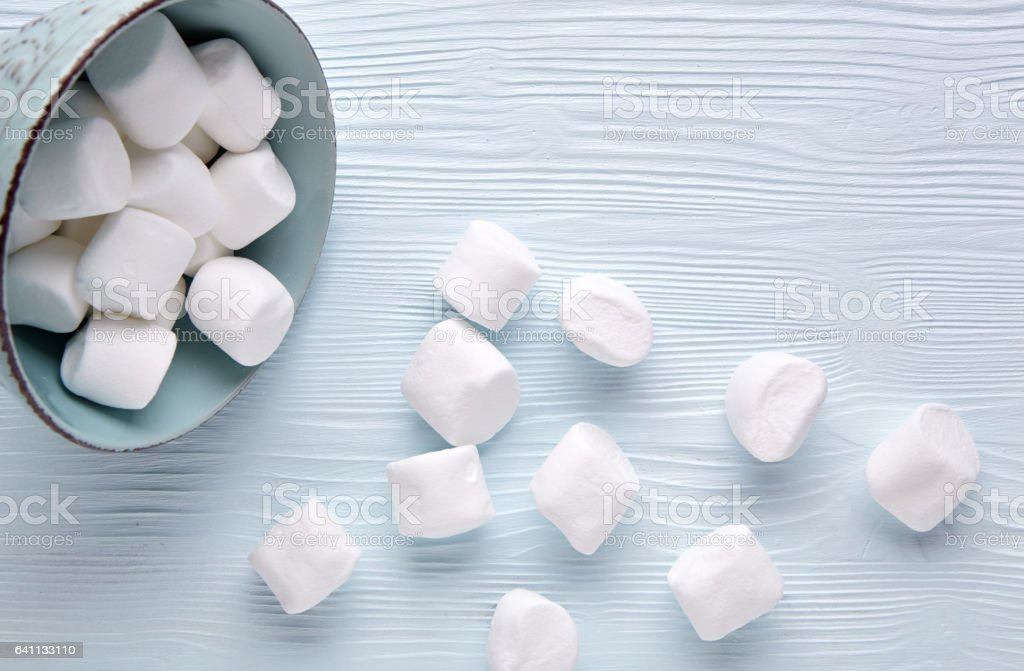 Marshmallow in a cup on a light wooden background. stock photo