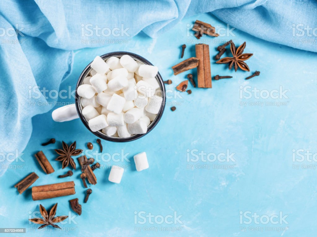 Marshmallows and winter spices on blue background stock photo