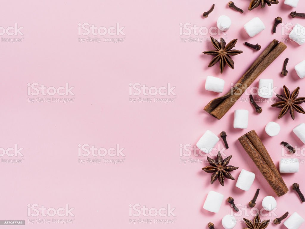 Marshmallows and winter spices on pink background stock photo