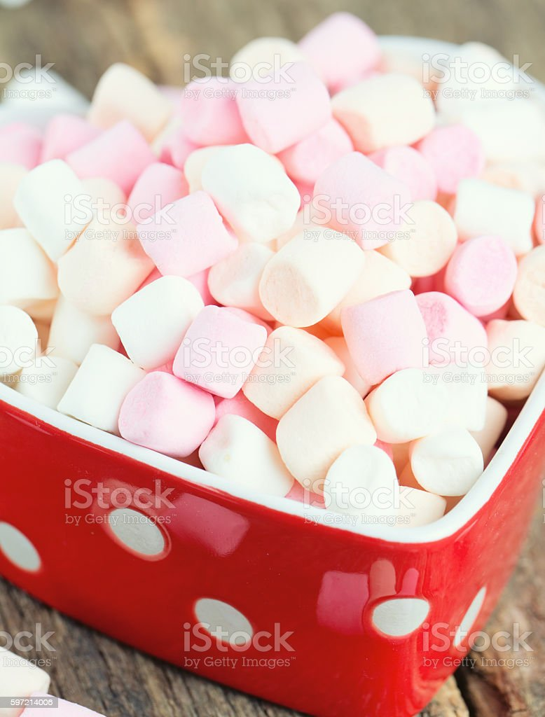 marshmallows in heart shape bowl on a wooden table stock photo